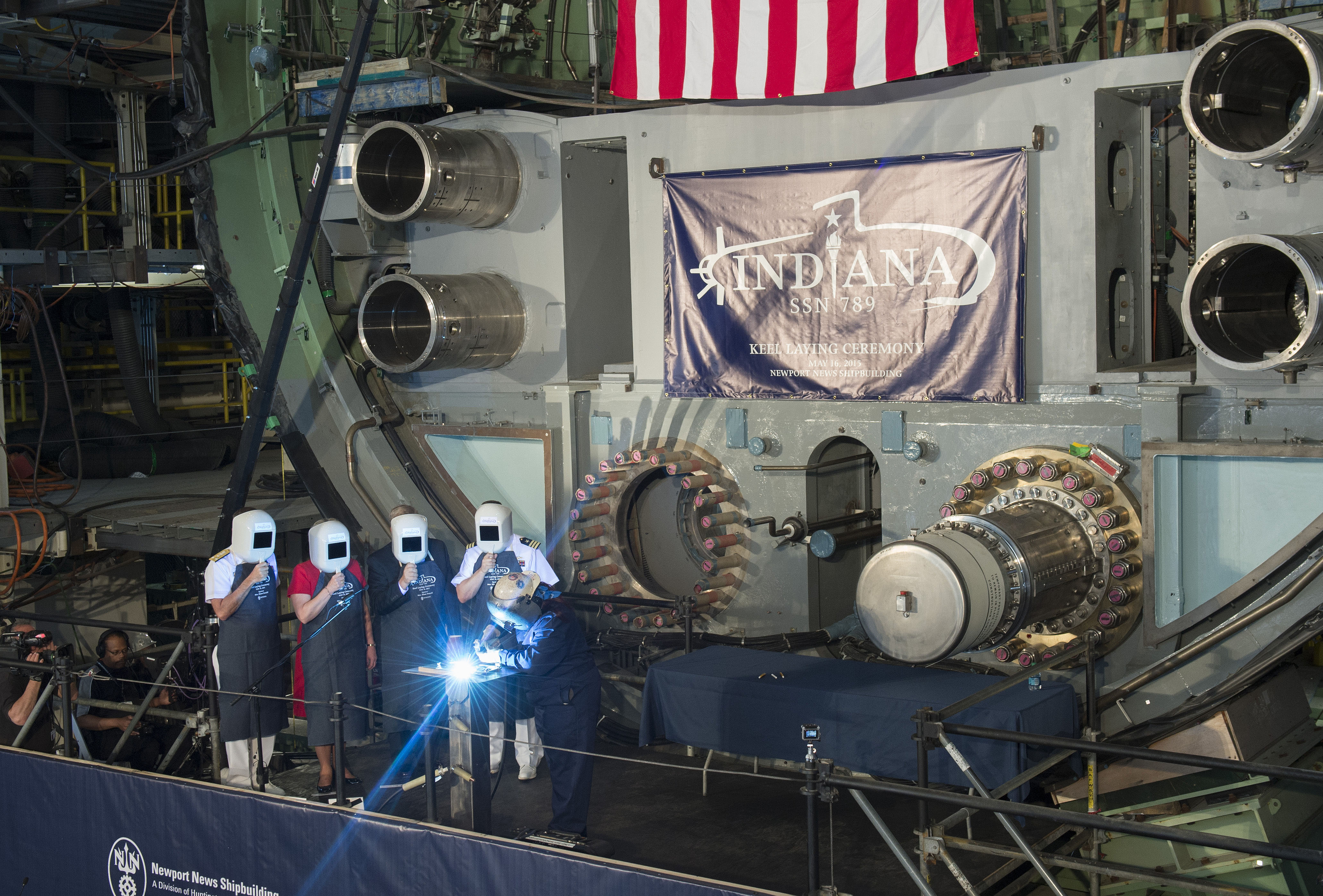 Heather Johnson carves the initials of ship's sponsor Diane Donald on a metal plate during the keel laying ceremony for the future Virginia-class attack submarine Indiana (SSN 789).