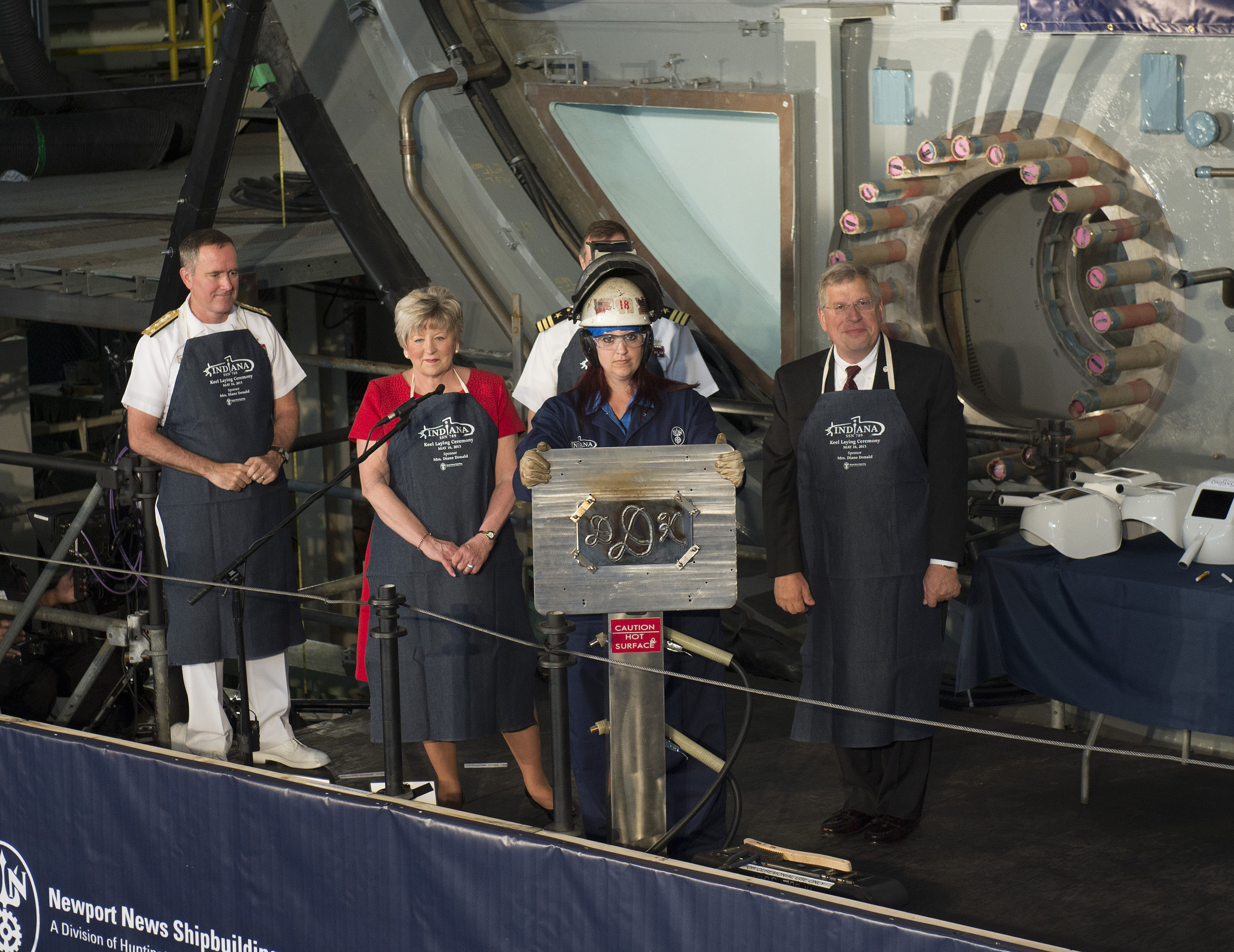 Heather Johnson shows ship's sponsor Diane Donald initials during a keel laying ceremony for the future Virginia-class attack submarine Indiana (SSN 789).